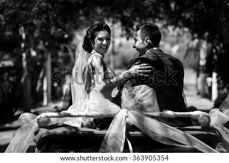 Beautiful stylish young successful couple enjoying riding in the car at wedding walk in the tropical country or island