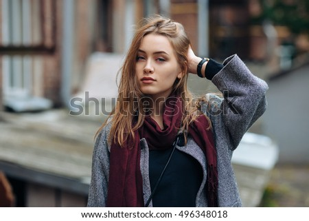 Beautiful stylish young woman in a warm scarf blue jeans trendy cozy coat posing alone against abandoned yard in fall city outfit. Touching her hair. Retro film filter edit.