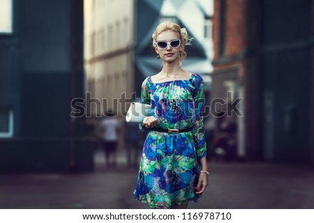 Beautiful stylish young woman on a street - stock photo