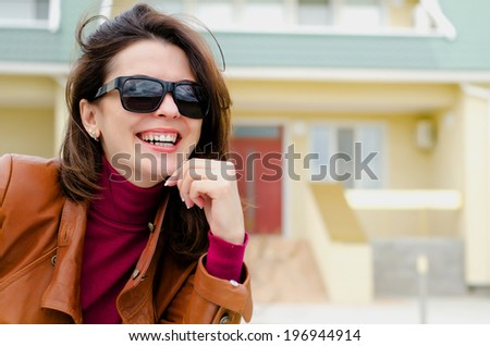 Beautiful stylish young woman sitting outside a house daydreaming with her chin resting on her hand staring up into the air with a faraway dreamy expression - stock photo