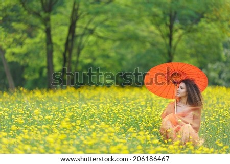 Beautiful stylish young woman with curly hair holding a colorful orange parasol in a meadow filled with yellow summer flowers as she clasps a chiffon scarf around her shoulders and looks to the side