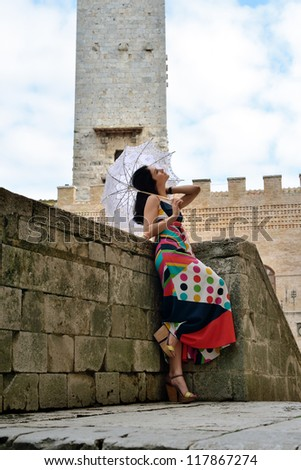 Beautiful stylish young woman with umbrella standing near the stone tower of the old castle, Tuscan, Italy - stock photo