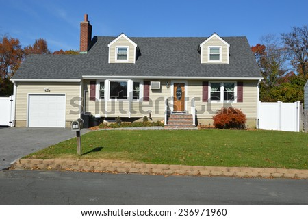 Beautiful Suburban cape cod style home autumn day residential neighborhood sunny clear blue sky USA - stock photo