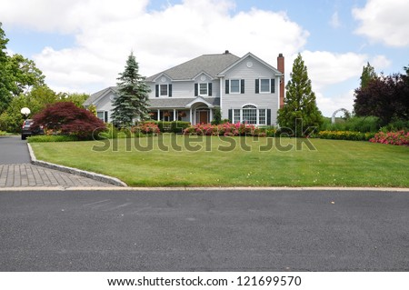 Beautiful Suburban Home Landscaped front yard with roses and daffodils - stock photo