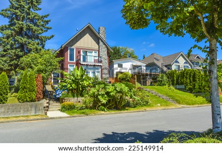 Beautiful suburban house over the street with landscaped terrace and blue sky background. Residential house at sunny day in British Columbia - stock photo