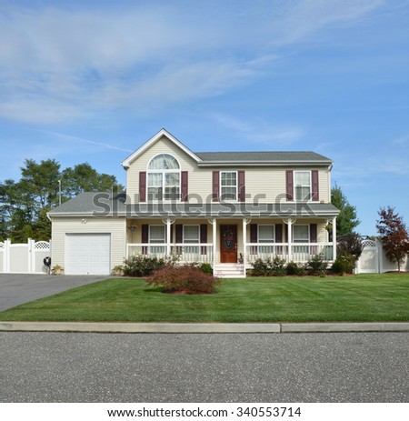 Beautiful Suburban McMansion Home Landscaped blue sky clouds residential neighborhood USA