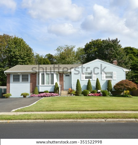 Beautiful suburban ranch style home with flowers residential neighborhood blue sky clouds USA