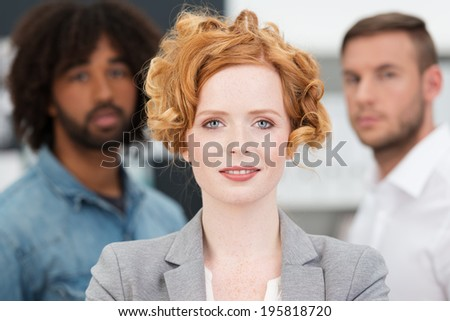 Beautiful successful female business team leader or manageress posing in front of her multiethnic male colleagues smiling at the camera