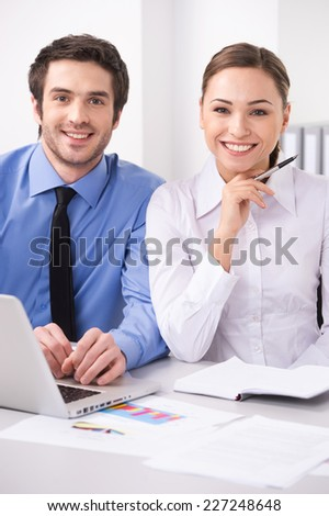 Beautiful successful young businesswoman with friendly smile. Two colleagues in office in front of computer  - stock photo