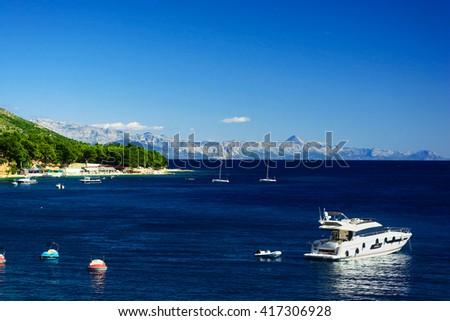 Beautiful Summer Adriatic Sea coastline view with mountains and white yacht, island Brac, Croatia - stock photo