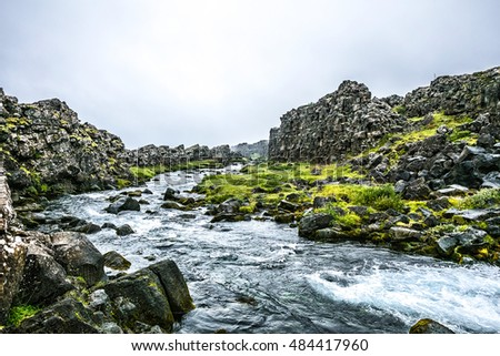 Beautiful summer brook with huge grey rocks and bright grass in Iceland