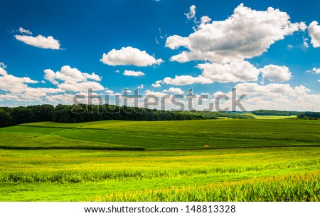 Beautiful summer clouds over fields and rolling hills in Southern York County, Pennsylvania. - stock photo