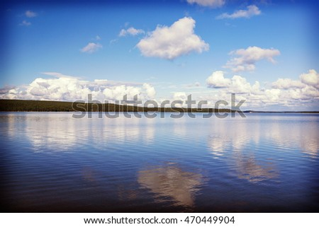Beautiful summer day in Finland. An image of big lake and deep blue sky with cloud formations. Some hills are in the background. Image has a vintage effect applied.
