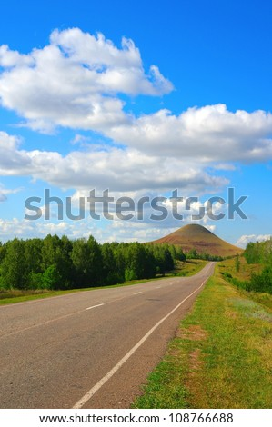 Beautiful summer landscape, road to high mountain, Blue sky with clouds
