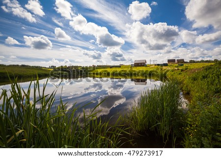 Beautiful summer landscape. The house on the lake. Sunny day. The water reflected the sky with beautiful clouds.