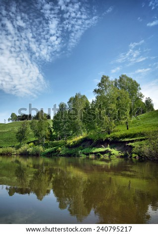 Beautiful summer landscape with calm little river and bright blue sky