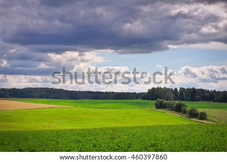 Beautiful summer landscape with green grass, road and clouds - stock photo
