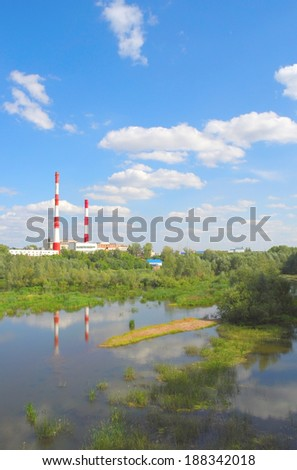 Beautiful summer landscape with river an factory chimneys