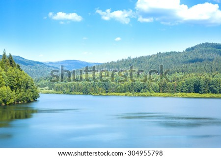 Beautiful summer mountain lake view and sunshine in sky - stock photo