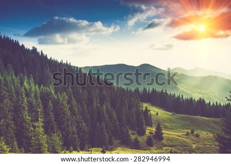 Beautiful summer mountain landscape at sunshine. Tourist tents near forest. Filtered image:cross processed vintage effect. - stock photo