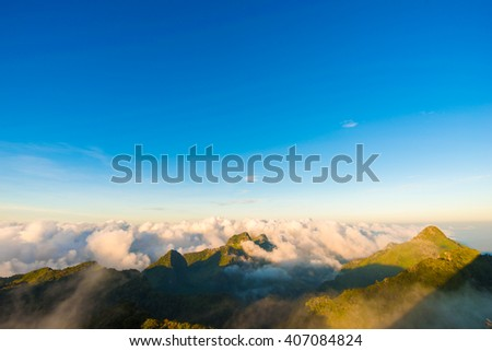 Beautiful summer sunrise on the top of mountain with Rays of Light, fog and cloud mountain - stock photo