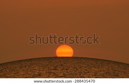 Beautiful summer sunset at sea - large bright orange sun sets over the horizon of the Black sea, Crimea - stock photo