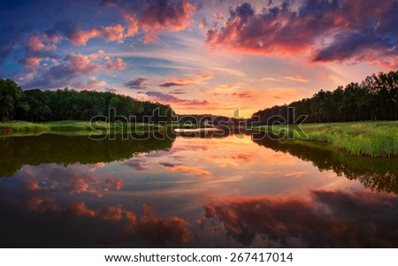 Beautiful summer sunset at the river with blue sky, red and orange clouds, green trees and water with reflection  (Ukraine) - stock photo