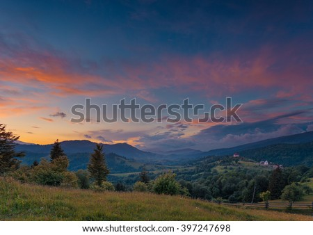 Beautiful summer sunset landscape in Carpathian mountains. Ukraine. Green pasture with wildflowers and shepherds house in the middle ground. Small private hotel as small detail far away. - stock photo