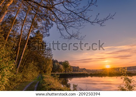 Beautiful summer sunset on the lake near the forest - stock photo