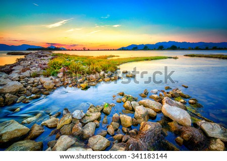 Beautiful summer sunset over the rocky shore by the sea. HDR image - stock photo