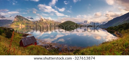 Beautiful summer sunset panorama of Lofoten Islands, Norway, with mountains, fjord, and small red rorbu used as fishing lodge. - stock photo