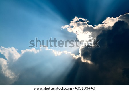 Beautiful sunbeam through the black stormy cloud.  - stock photo