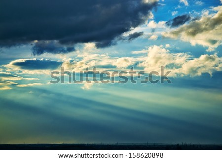 Beautiful sunbeams on the sky over distant landscape at the sunset - stock photo
