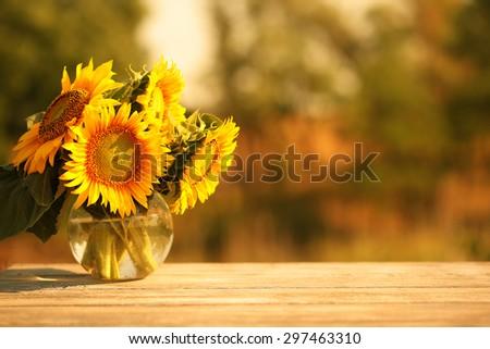 Beautiful sunflowers on table outdoors - stock photo