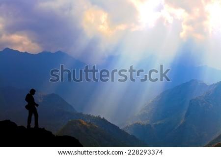 Beautiful Sunlight Rays on mountain with Landscape Photographer, Copyspace - stock photo