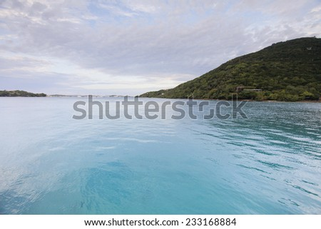 Beautiful Sunny Day Over The Caribbean Sea With Islands, Clouds, Blue Skies, Clear Blue Water, And Green Plants. - stock photo
