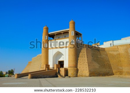 Beautiful sunny day view of ancient fortress - The Ark and the ceremonial entrance into it against the background of blue sky in Historic Center of Bukhara, Uzbekistan, Central Asia - stock photo