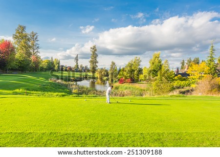 Beautiful sunny green golf course with pond in Vancouver, Canada. A man playing golf. - stock photo