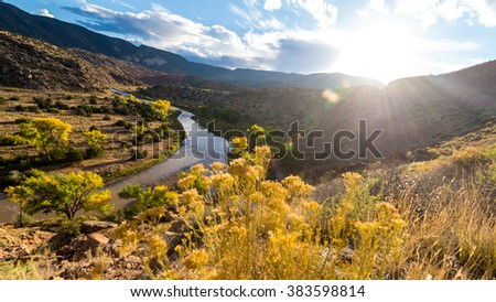 Beautiful sunny walley landscape with wide mountain creek between the yellow trees with cloudy blue sky  - stock photo