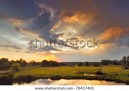Beautiful sunrise and dramatic clouds on the sky. Flood waters of Narew river, Poland. - stock photo