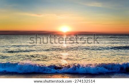 Beautiful sunrise and sea beach in Sozopol, Bulgaria. Black sea. Waves hit the shore. Amazing colors. - stock photo