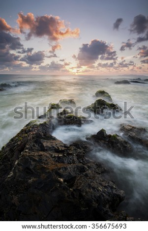 beautiful sunrise at rocky beach with waves. image may have slight noise and softness due to long exposure,custom white balance applied