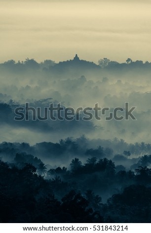 Beautiful sunrise from Setumbu Hills with a view of Mount Merapi Volcano and Borobudur Buddhist Temple (UNESCO World Heritage Site) - Java, Indonesia