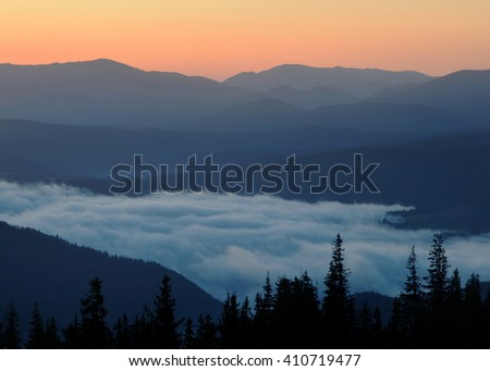 Beautiful sunrise in mountains. White mist are in the middle of composition.