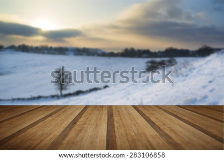 Beautiful sunrise landscape over snow covered Winter countryside with wooden planks floor - stock photo