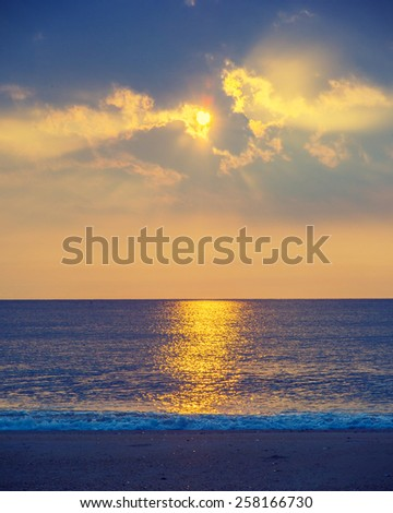 Beautiful sunrise on Sandy Hook Beach, New Jersey, USA. Scenic view over Atlantic ocean, sun, horizon and running waves, peaceful, lovely and dramatic. Instagram filtered look.  - stock photo