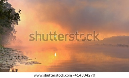 Beautiful sunrise on the river. sun in fog. copy space - stock photo