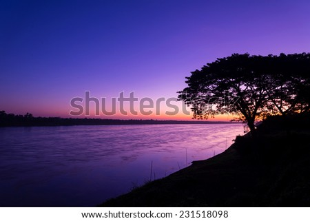 Beautiful sunrise out with silhouetted of tree at Mekong river, laos. - stock photo