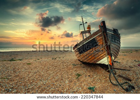 Beautiful sunrise over an old wooden fishing boat on a pebble beach, vintage effect. - stock photo