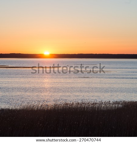 beautiful sunrise over country lake with orange clouds and reflections - stock photo